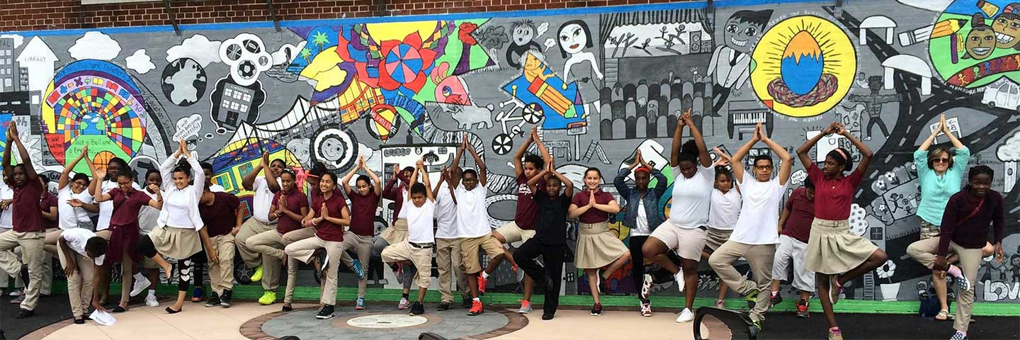 Students at Sussex Avenue School stand in front of a playground mural created during an AIE residency.
