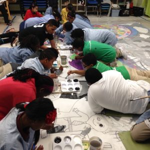 Sussex Avenue students paint sections of their playground mural on parachute cloth that will later be attached to the exterior of the school building.